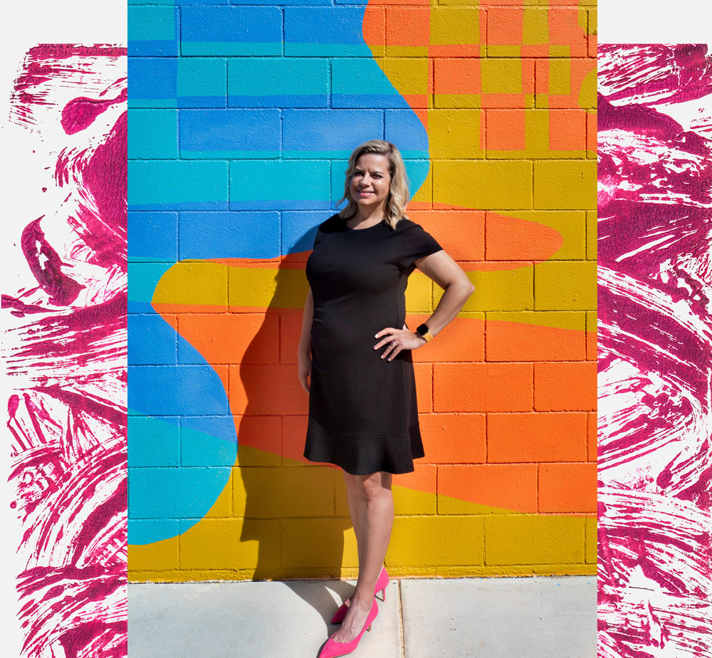 Lisa Burford stands in front of a colorful wall mural in Palm Springs, California