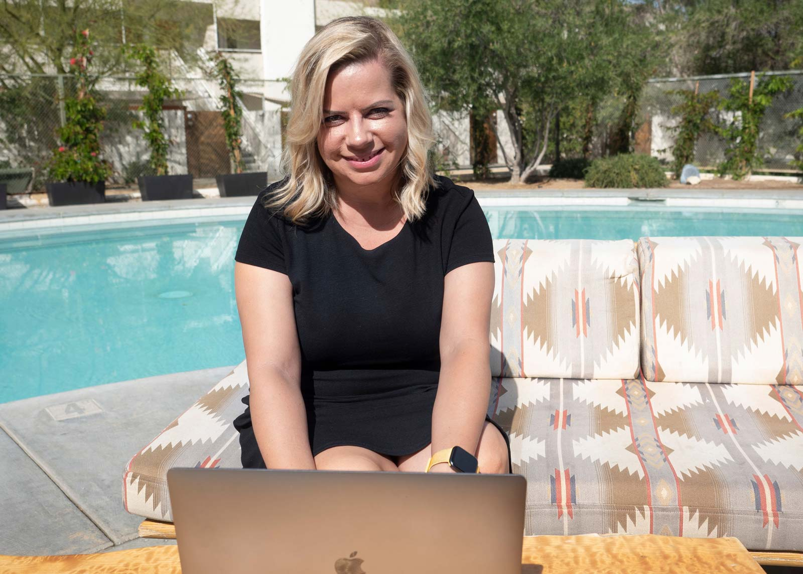 Lisa Burford working on a laptop while sitting by a pool in Palm Springs, California