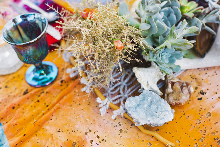 Wedding centerpiece on a table with succulents, rocks, crystals, and Mojave Macrame table runner